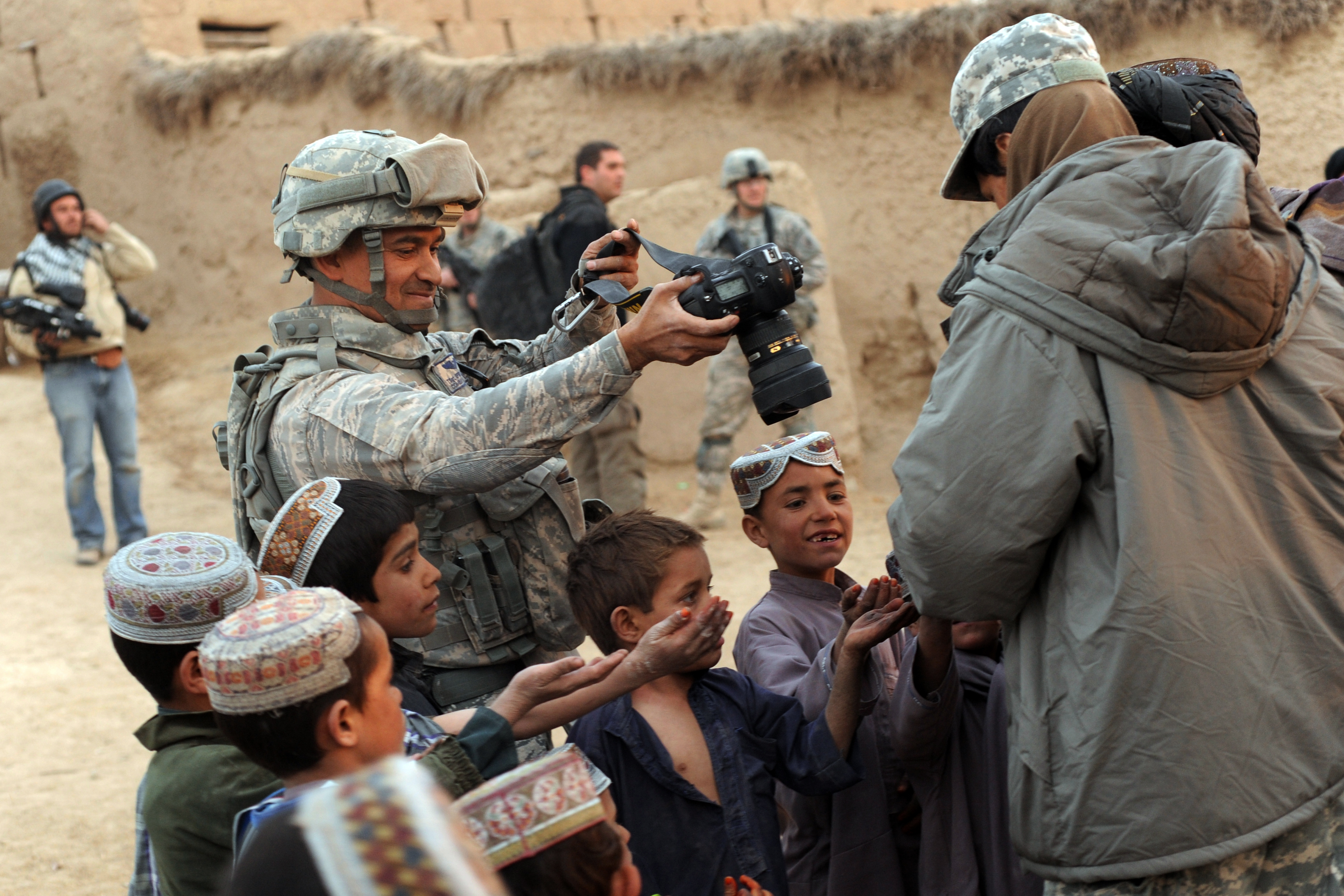 Description Combat Camera in Afghan village.jpg