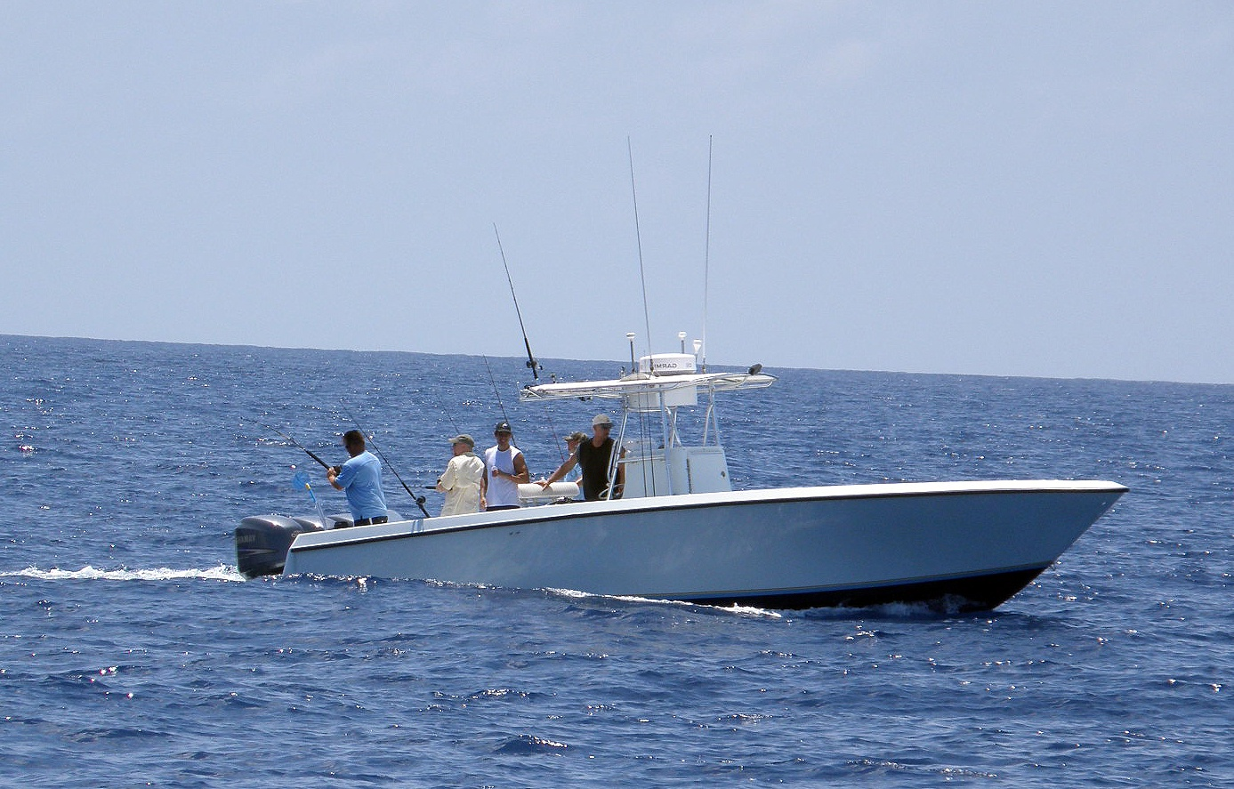Several people fishing from a boat in open water.